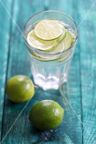 A glass of water with limes
