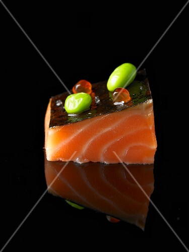 An amuse bouche with salmon on a black surface