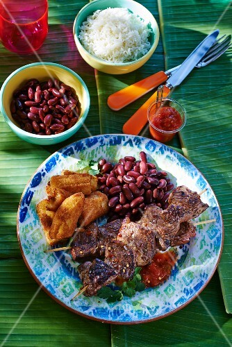 Grilled meat skewers with baked bananas and kidney beans