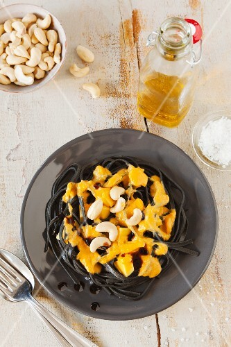 Black tagliatelle with pumpkin sauce and cashew nuts