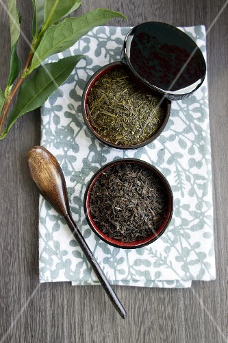 Wooden tea bowls with green and black tea leaves