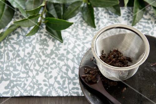 Used black tea leaves in a tea strainer