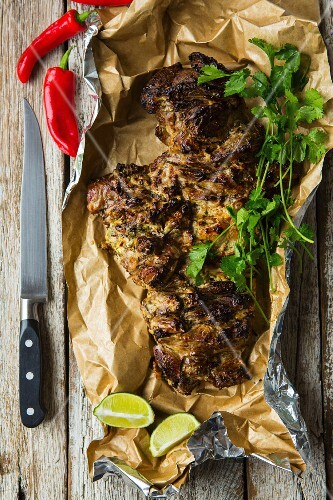 Roasted, sliced leg of lamb with coriander, chilli and limes on a wooden table