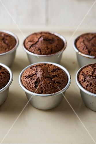 Warm fondants au chocolate in baking tins on a baking tray