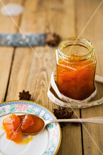 A jar of homemade apricot jam with a printed ribbon and star anise