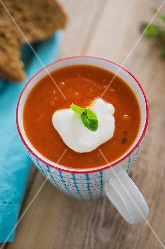 Tomato and pepper soup served in a mug with créme fraîche, fresh basil and crusty bread