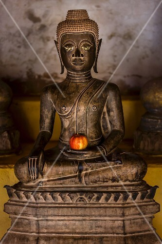 An apple on a Buddha statue as an offering in a temple (Vientiane, Laos)
