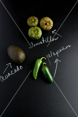 An avocado, jalapeños and tomatillos on a slate surface with labels