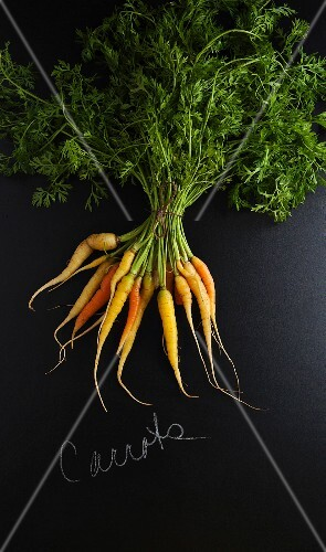 Carrots on a slate surface with a label