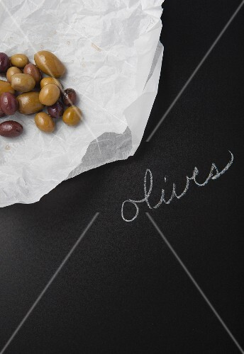 Olives on a piece of paper on a slate surface with a label