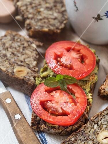 Flourless bread with sunflower, flax and chia seeds, oats, psyllium seed husks and hazelnuts, served with pesto and fresh tomatoes