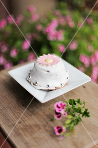 A mini cake with a flower decoration and silver pearls