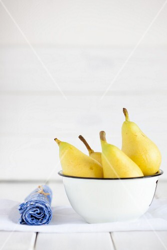 Four yellow pears in a bowl