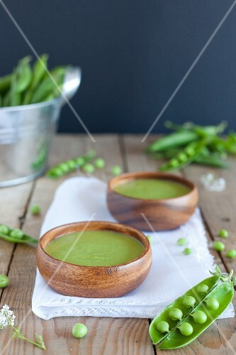 Two bowls of pea soup and fresh peas