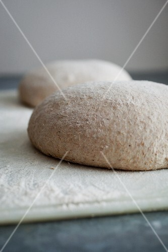 Two balls of dough for sourdough loaves, sprinkled with flour