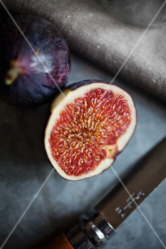 A whole fig and a halved fig on a galvanised surface with a linen cloth and a knife