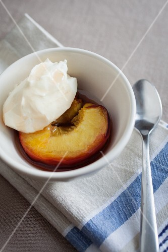 A honey-roasted peach with crème fraîche in a small white bowl