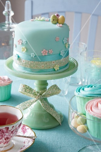 A cake decorated with pastel-coloured fondant on a cake stand for an Easter party