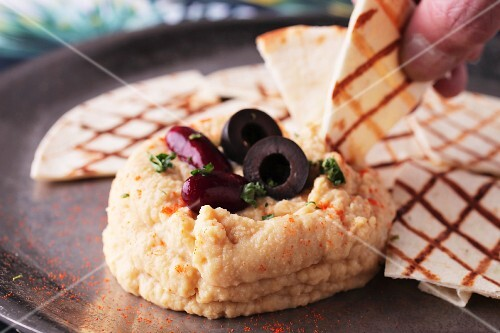 A hand dipping unleavened bread in hummus