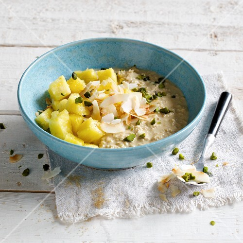 Oat cream with a pineapple salad, coconut chips and pistachio nuts