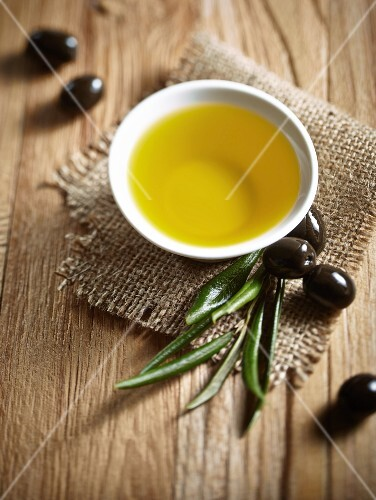 A bowl of olive oil, black olives and a spring of olive leaves