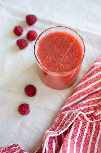 A red berry smoothies with raspberries in a glass