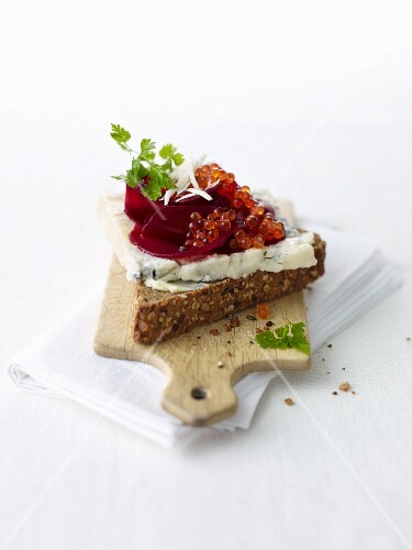 A slice of bread topped with blue cheese, beetroot and caviar