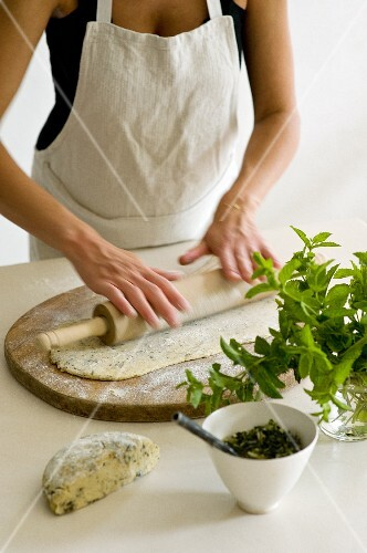 Bread dough being rolled out with a rolling pin