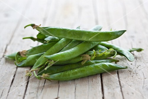 Fresh pea pods on a wooden surface
