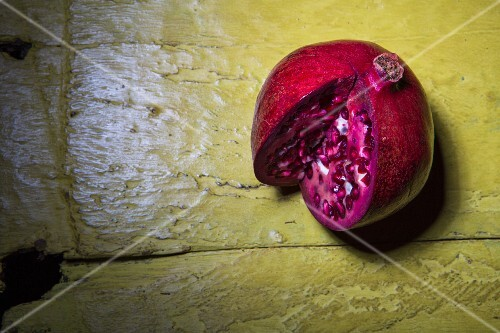 A sliced pomegranate on a rustic yellow wooden surface