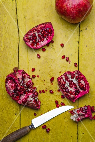 Pomegranates, whole and chopped, on a rustic yellow wooden surface