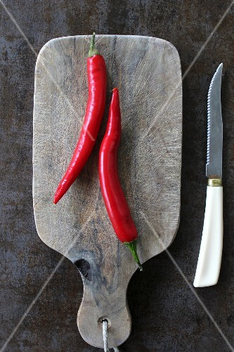 Two red chilli peppers on a chopping board (seen from above)