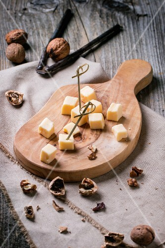 Small cubes of cheese on an olive wood chopping board with walnuts