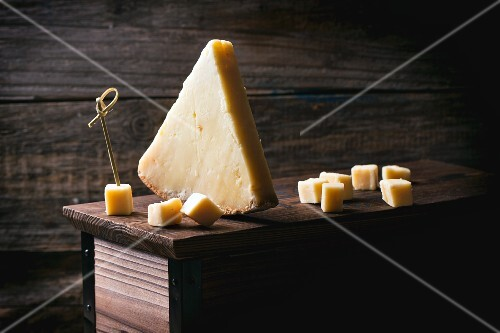 A piece of Belgian cheese and cubes of cheese on a wooden box