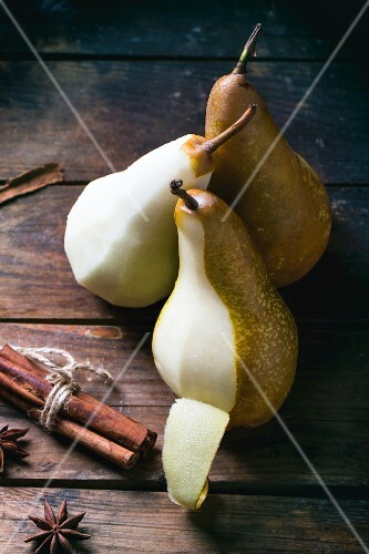 Partially peeled pears with spices on a wooden table