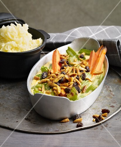 Gratinated celery with carrots, raisins and flaked almonds