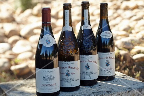 Bottles of red wine with the coats of arms of the Beaucastel vineyard in Appellation Chateauneuf-du-Pape, France
