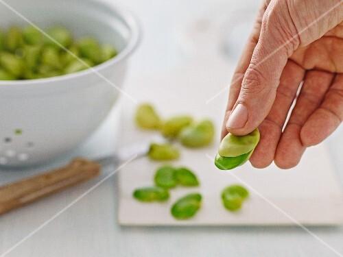 Broad beans being peeled