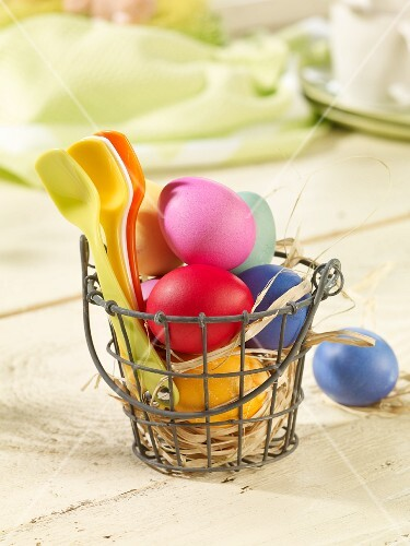 Colourful Easter eggs and plastic spoons in a wire basket lined with straw