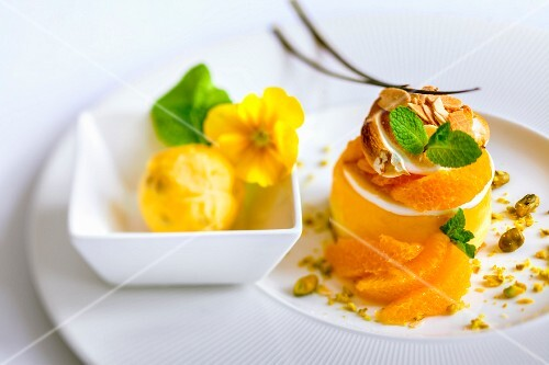 A mini orange tart with meringue, flaked almonds and mint