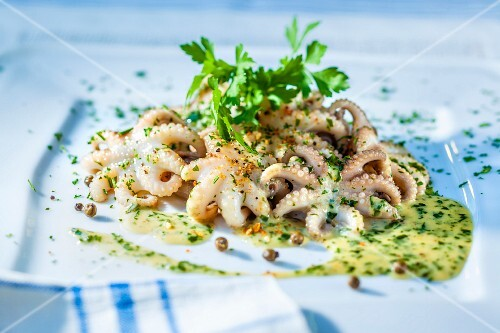 A small octopus in herb sauce with capers