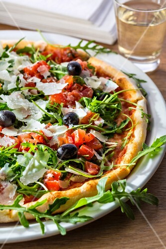 Pizza bruschetta with olives, cheese, rocket and tomato