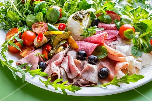 An anti-pasti platter with roast beef, cold cuts, cherry tomatoes and olives