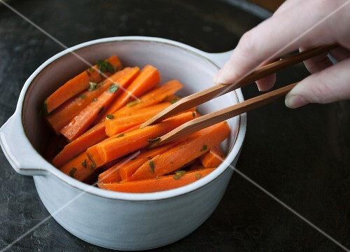Cooked carrots being removed from a saucepan with a pair of tongs