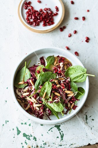 Spinach salad with pomegranate seeds, radicchio and pine nuts