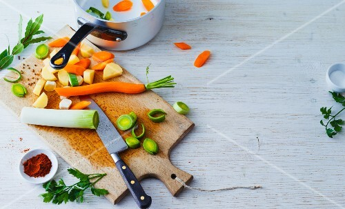 Sliced soup vegetables on a chopping board with spices and herbs