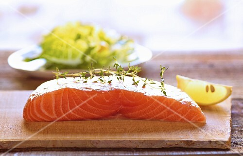 Raw salmon fillet on a chopping board with thyme and lemon