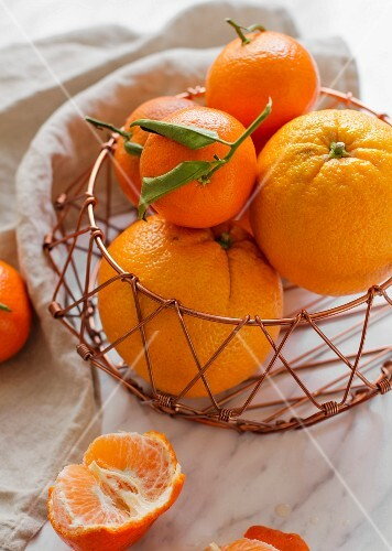 Fresh oranges and clementines in a wire basket