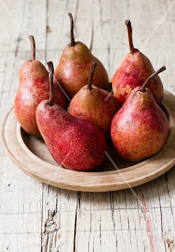 Red pears on a wooden plate