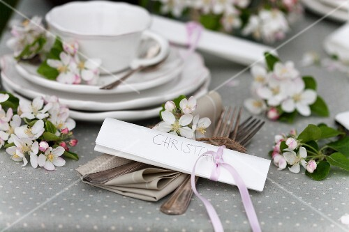 A place setting decorated with apple blossom and a place card